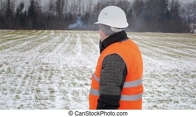 Forest inspector with cell phone near smoke in the woods