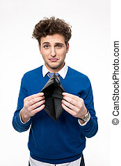 Upset young man holding emty wallet over white background