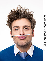 Young funny man holding a pencil between the lips and nose