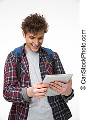 Happy male student standing with tablet computer
