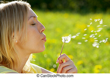 Spring entertainments - The girl blows on a dandelion on a...