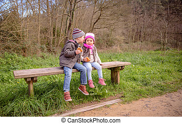 Boy talking to the ear of little girl sitting on bench -...