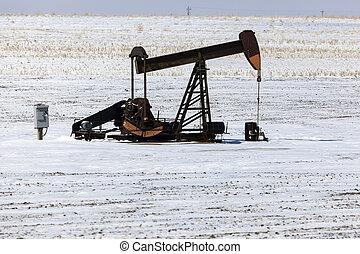Oil well pump winter time. Kansas, USA.
