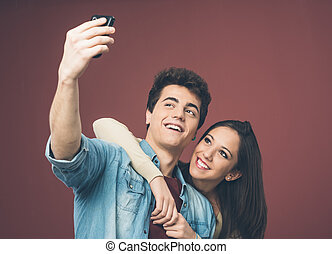 Young couple taking selfies - Young cheerful couple taking...
