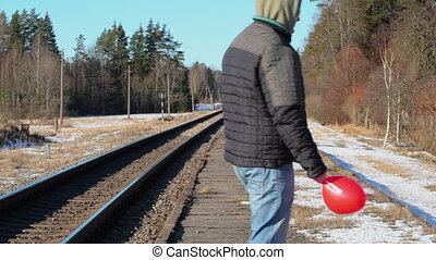 Man with red heart-shaped balloon near railway