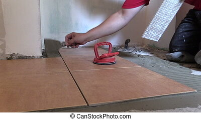 worker place tiles - Construction worker place floor tiles...