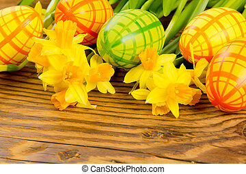 Easter eggs with daffodil blooms on wooden board