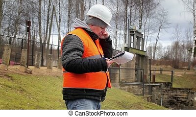 Engineer talking on cell phone at power plant sluice