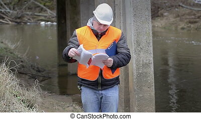 Engineer reading the documentation under the bridge
