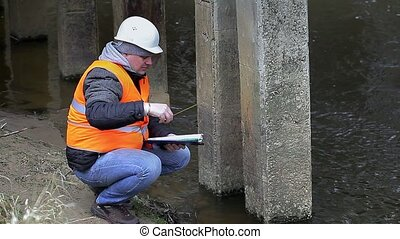 Engineer with tape measure and documentation under the...