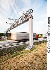 truck passing through a toll gate on a highway (motion...