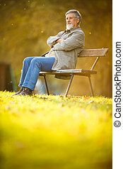Portrait of a senior man outdoors - Senior man sitting on a...