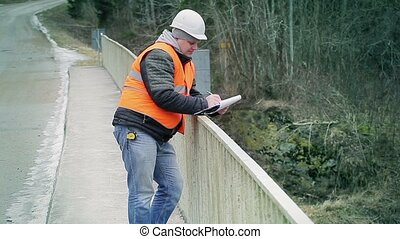 Engineer writing documentation on the bridge