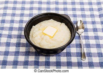 White Grits in Black Bowl with Butter - A black bowl with...