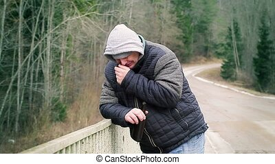 Sorrowful man with beer bottle on the bridge
