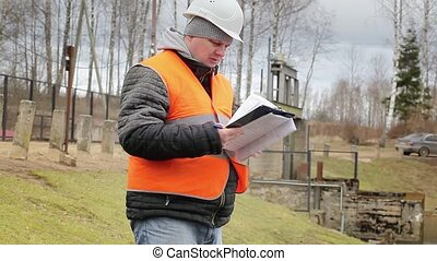 Engineer reading documentation at power plant sluice