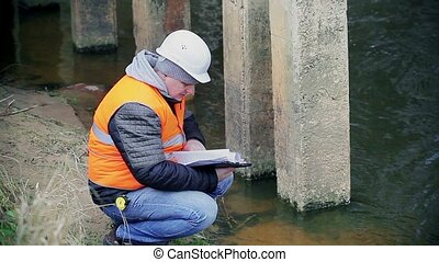 Engineer checking documentation near the bridge supports