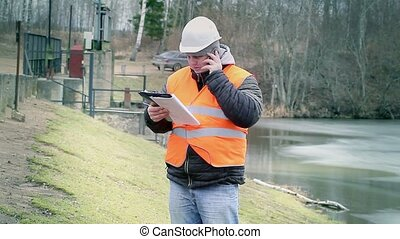 Engineer with cell phone and documentation at power plant...