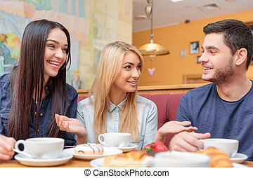Beautiful young people in the cafe - Enjoying coffee with...