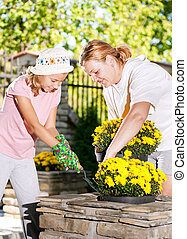 planting flowers - Mom and daughter planting flowers in pots