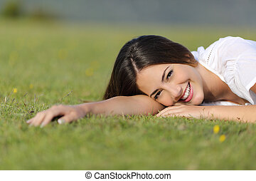 Happy woman smiling and resting relaxed on the grass