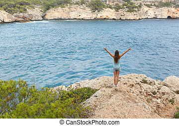 Happy free teenager raising arms on vacations