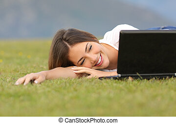 Happy woman watching videos in a laptop lying on the grass