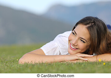 Pretty happy woman thinking on the grass and looking at side...