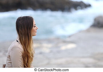 Profile of a pensive woman on the beach in winter - Profile...