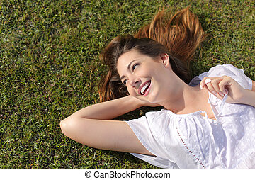 Happy relaxed woman lying on the grass