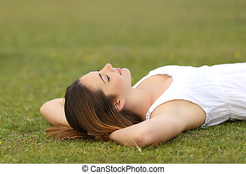 Relaxed woman lying on the grass sleeping in a tranquil scene
