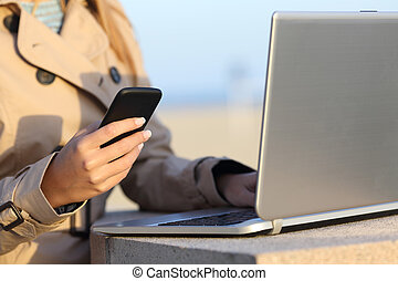 Self employed woman working with a laptop and phone -...