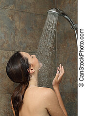 Woman enjoying the water in the shower under a water jet...