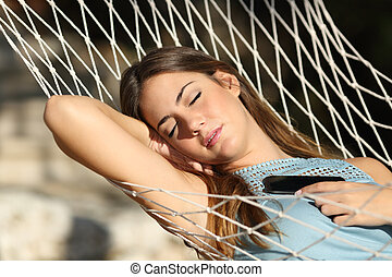 Woman sleeping and resting on a hammock with a mobile phone...
