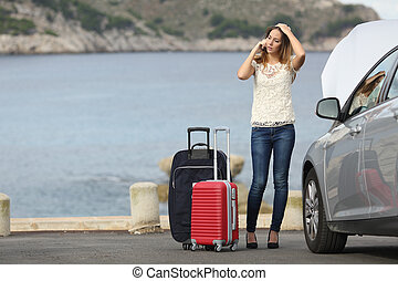 Worried traveler woman calling assistance with a breakdown...