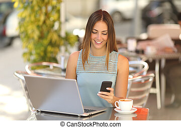Entrepreneur working with a phone and laptop in a coffee...