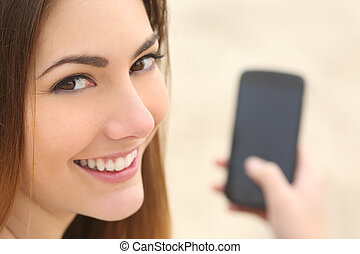 Portrait of a smiley woman using a smart phone - Close up...