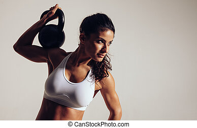 Focused young woman doing crossfit workout with kettle bell...