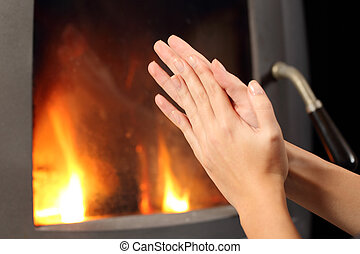 Woman hands heating in front a fire place - Woman rubbing...
