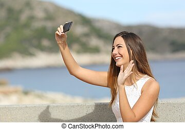 Woman greeting while photographing a selfie with a...