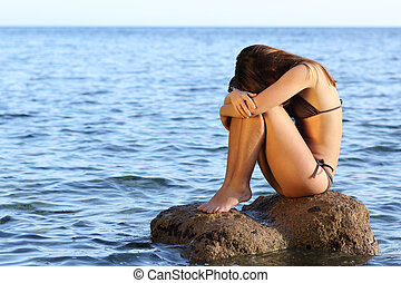Worried woman sitting on a rock on the beach - Lonely...