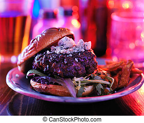gourmet burger at pub or bar with colorful lighting