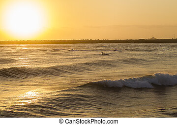 Surf-Ski Paddler Ocean Sunrise - Surf-ski paddlers at...