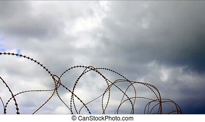 Barbed wire on clouds background - Barbed wire trembling in...