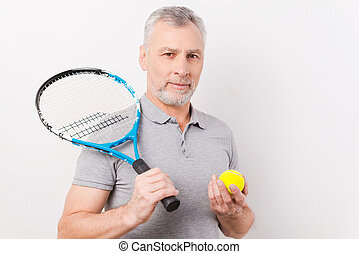 Ready to play. Confident grey hair senior man holding tennis...