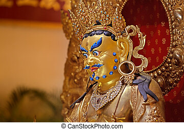 guardian deity - close up of golden statue inside a buddhist...