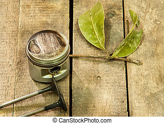Old piston and dry leaf laying on the wooden floor