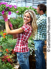 Gardening people Couple working in greenhouse with flowers