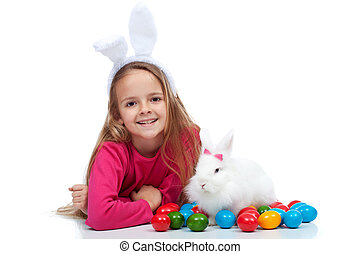 Happy girl with her easter rabbit and colorful dyed eggs -...