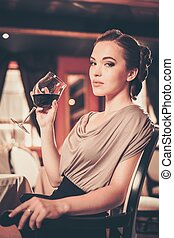 Young woman with glass of red wine alone in a restaurant